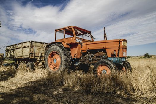 meadow, old agricultural tractor abandoned in a farm field