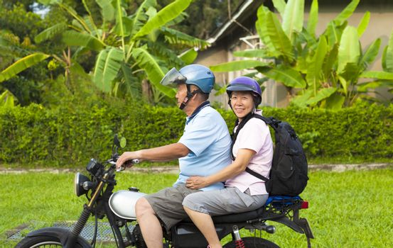 asian senior couple driving motorcycle to travel