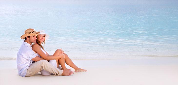 Beautiful loving couple sitting on the beach, spending honeymoon on Maldives, relaxation on summer resort, love concept
