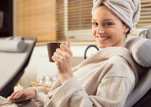 Young woman smiling and relaxing at spa, holding an hot healthy drink.