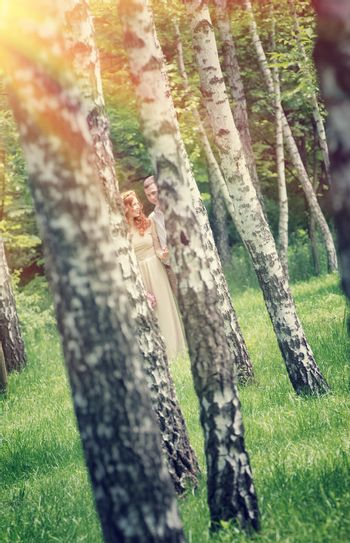 Photo of young couple through two birch trees, having fun in the park, bright sun rays, romantic relationship, summer holidays, affectionate concept
