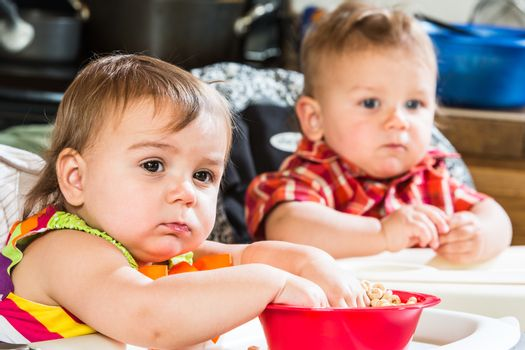 Two cute babies are eating breakfast together