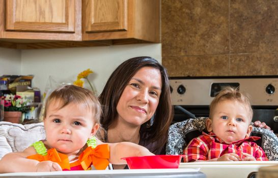 A mother in the kitchen poses with babies