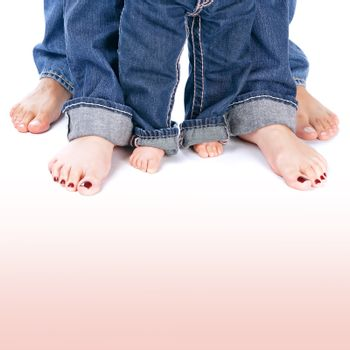 Mother, father and little child wearing blue jeans, barefoot people legs isolated on white background, body part, family togetherness concept