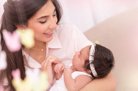Portrait of beautiful young female holding on hands cute newborn daughter, enjoying motherhood, soft focus, happy family concept
