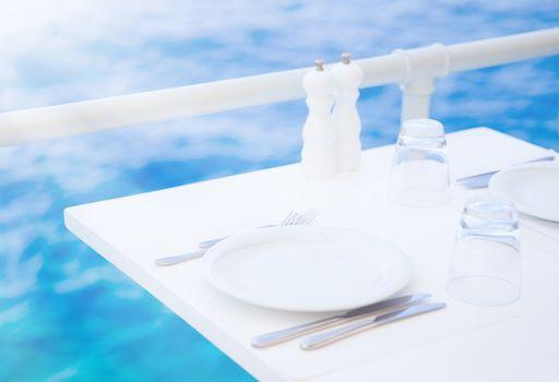 Romantic dinner in outdoor restaurant on the beach, festive white tableware, wedding celebrating on summer terrace