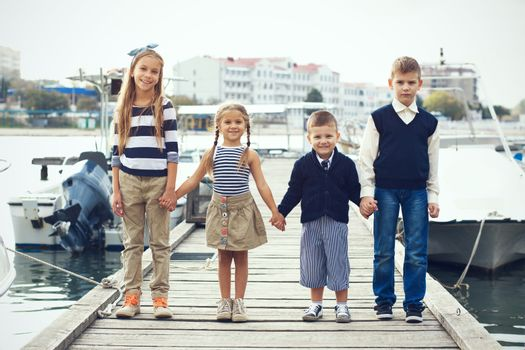Group of 4 fashion kids wearing navy clothes in marine style posing in the sea port and holding hands