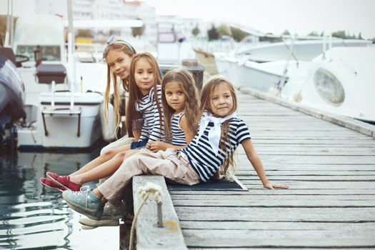 Group of 4 fashion kids wearing navy clothes in marine style walking in the sea port
