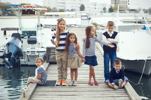 Group of 6 fashion kids wearing navy clothes in marine style walking in the sea port