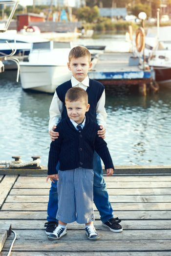 Fashion kid boys wearing navy clothes in marine style posing in the sea port