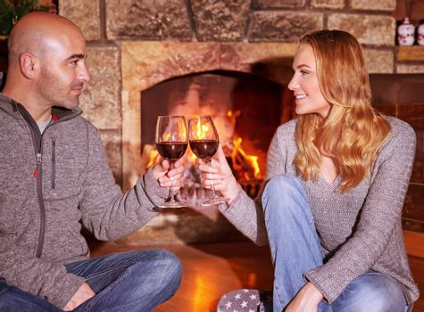 Happy young couple sitting near fireplace and drinking wine, enjoying romantic date, celebrating Valentines day in luxury cozy winter resort