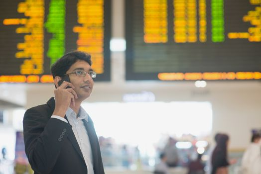 Asian Businessman on the phone during his business travel, at the airport .