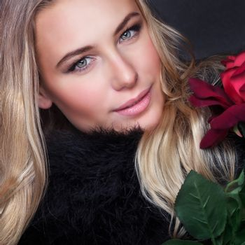 Closeup portrait of attractive gorgeous woman with red flower, Valentine day, luxury beauty salon, fashion and vogue concept