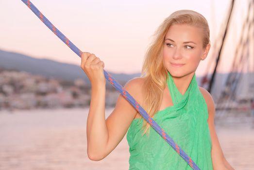 Romantic sea cruise, portrait of cute blond girl enjoying evening traveling on luxury sail boat, summer holidays concept