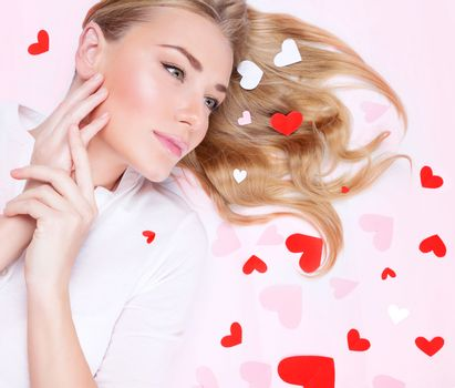 Closeup portrait of a beautiful romantic woman lying down on pink  background, many little red hearts on blond hair, Valentine's day concept