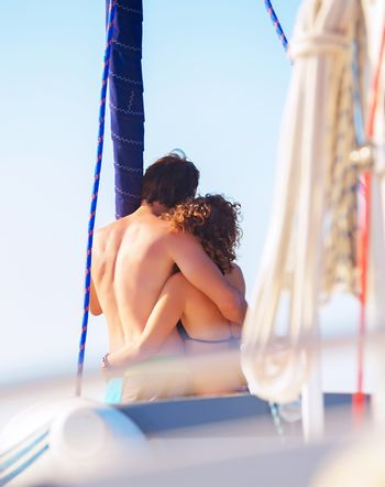 Back side of happy loving couple standing on the mast of luxury sail boat and hugging, enjoying sea view and summer vacation, love concept
