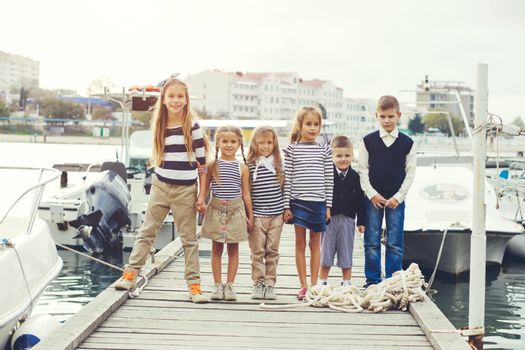 Group of five fashion kids wearing navy clothes in marine style posing in the sea port and holding hands