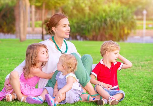Portrait of happy mother with cute little babies sitting on fresh green grass field, looking away, having fun outdoors, enjoying parenthood, happiness and love concept