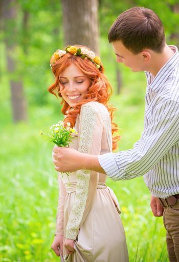 Happy loving couple in the park, handsome guy giving cute wildflower bouquet to his girlfriend, tender feelings and romantic relationship