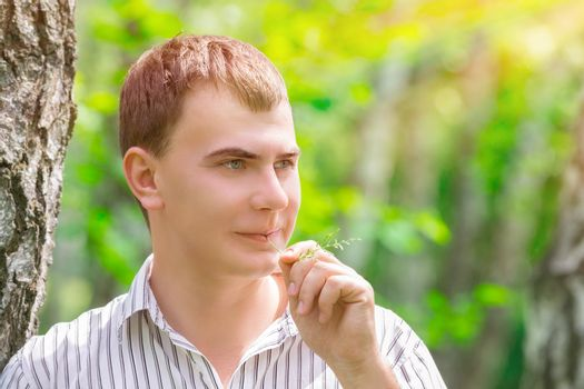 Closeup portrait of romantic guy in the park, standing near birch tree with straw in the mouth, waiting for his girlfriend, enjoying beauty of spring nature