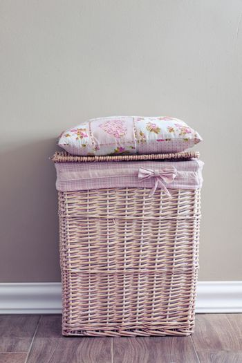 Interior detail. Wicker basket and pillow on it.
