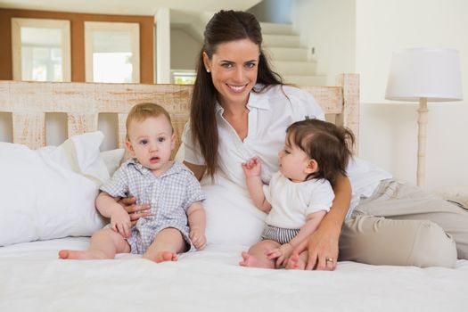 Happy mother with cute babies boy and girl at home in bedroom