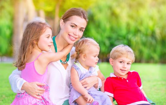 Portrait of happy mother with cute little babies sitting on fresh green grass field, having fun outdoors, enjoying parenthood, happiness and love concept