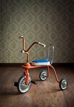 Vintage orange tricycle on hardwood floor and vintage wallpaper on background.