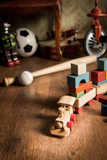 Wooden train and vintage colorful toys on hardwood floor and retro wallpaper on background.