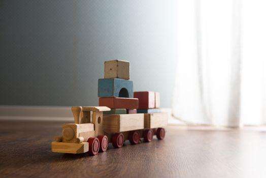 Vintage wooden toy train next to a window on hardwood floor.