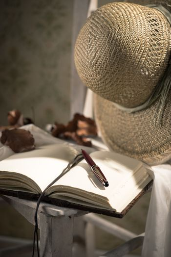 Elegant open book with pen, straw hat and dry leaves.