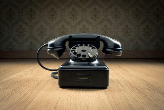 Black 1950s style phone on hardwood floor and vintage wallpaper on background.