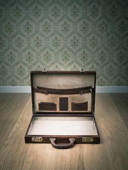 Open vintage leather briefcase on hardwood floor, retro wallpaper on background.