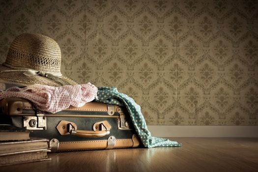 Holiday packing with vintage suitcase and polka dot clothing on hardwood floor.