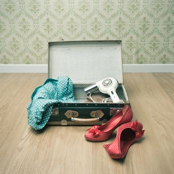 Open vintage suitcase with red shoes and dotted clothing, retro wallpaper on background.