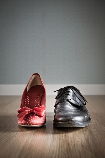Male and female elegant shoes on hardwood floor with vintage wallapaper on background.