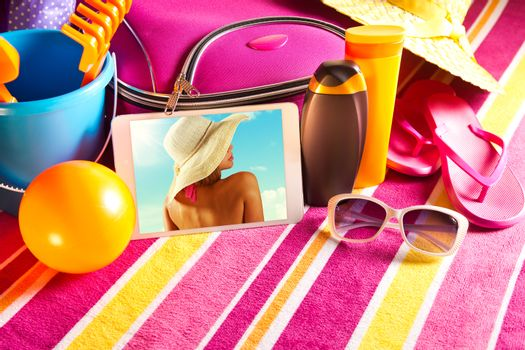 Tablet showing vacations pictures with towel, sunglasses, sun creams and beach accessories.