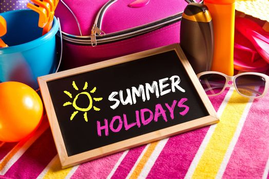 Happy summer holidays card with colorful text on blackboard.