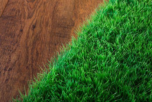 Artificial lush grass close-up on wooden hardwood floor.