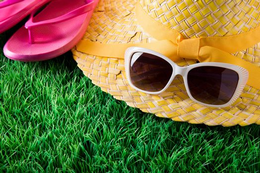 Sunglasses, straw hat and pink fli flops on lush green grass, vacations concept.