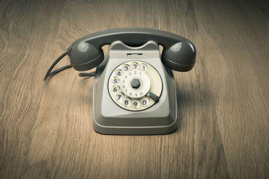 Vintage gray telephone on hardwood surface desk or floor.