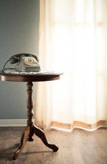 Vintage telephone on doily and wooden table in the living room next to a window.