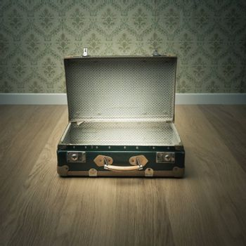 Open vintage suitcase on wooden floor with vintage wallpaper on background.