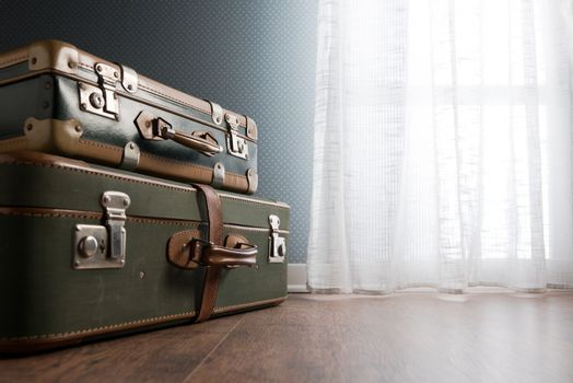 Pile of vintage suitcases next to a window on hardwood floor.