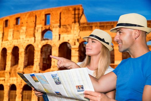 Beautiful active couple with map standing on Coliseum background and looking for right way, travel to Rome and exploring it by themselves, Italy Europe