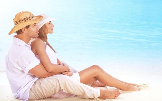 Beautiful couple on the beach, sitting on the coast and hugging, enjoying peaceful sunny day on tropical resort, romantic summer vacation