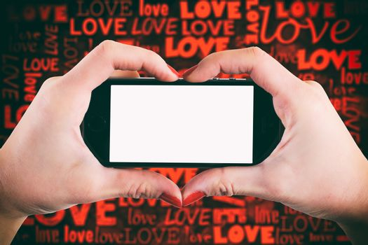 Female holding cell phone with blank screen and love background
