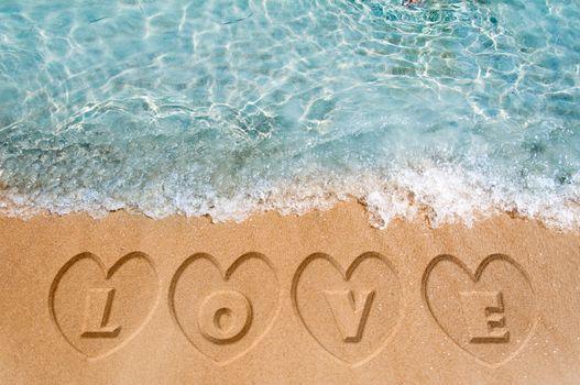 Love word sign on the beach sand