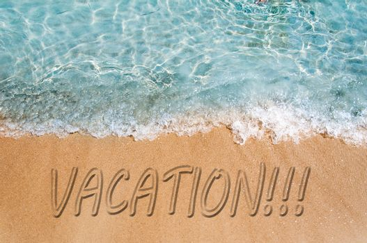 Vacation word sign on the beach sand