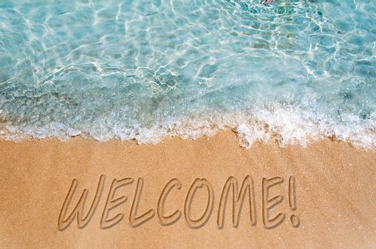 Welcome word sign on the beach sand